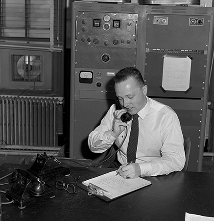 Man talking on telephone while writing at a desk in WERS studio